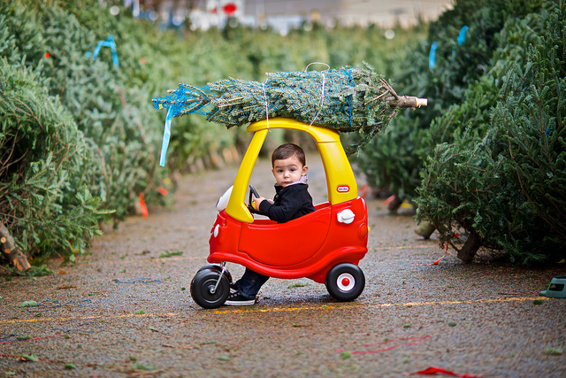 child driving plastic toy car with christmas tree on top