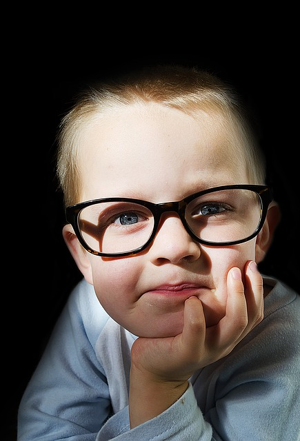 little boy in black glasses
