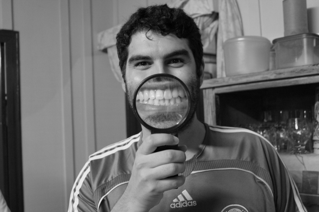 A man holds a magnifying glass up to his smile.