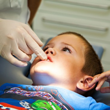 A child having his teeth examined by a dentist.