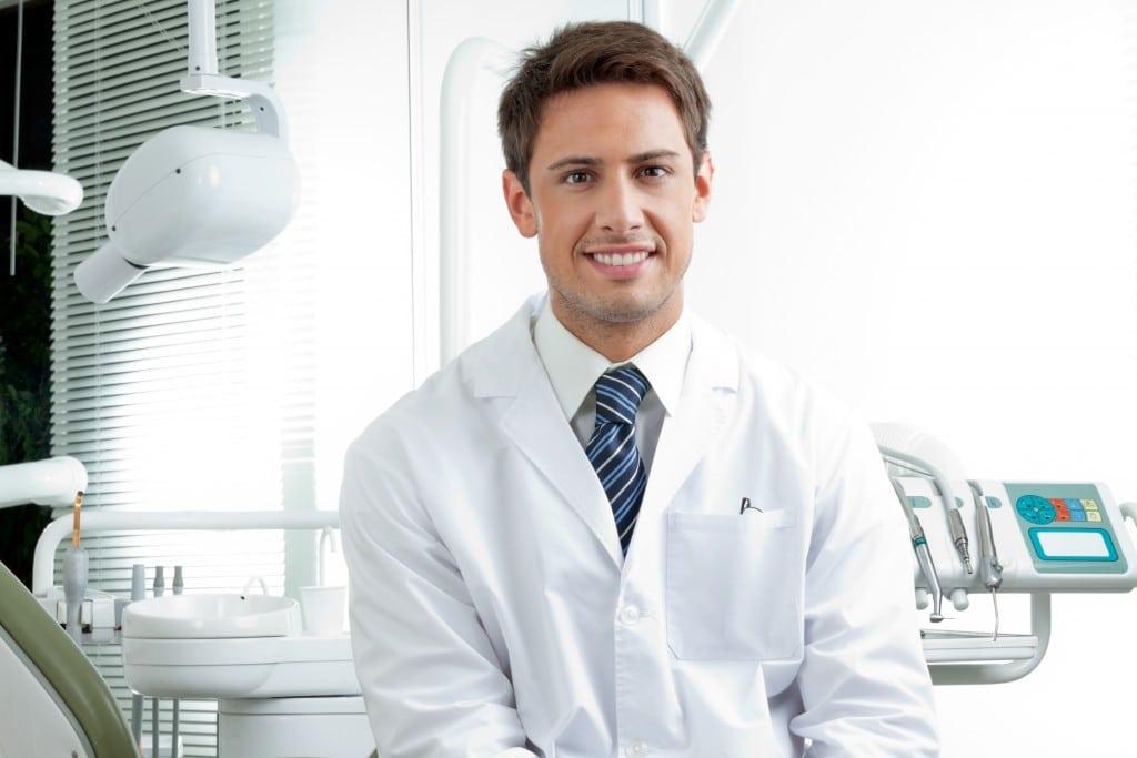 Male dentist in white coat