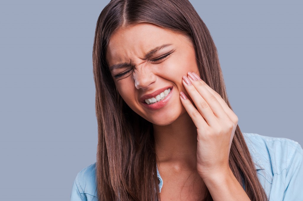 Girl touching face in tooth pain