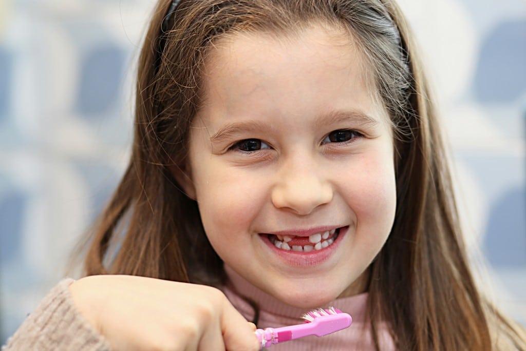 child smiling and holding tootbrush