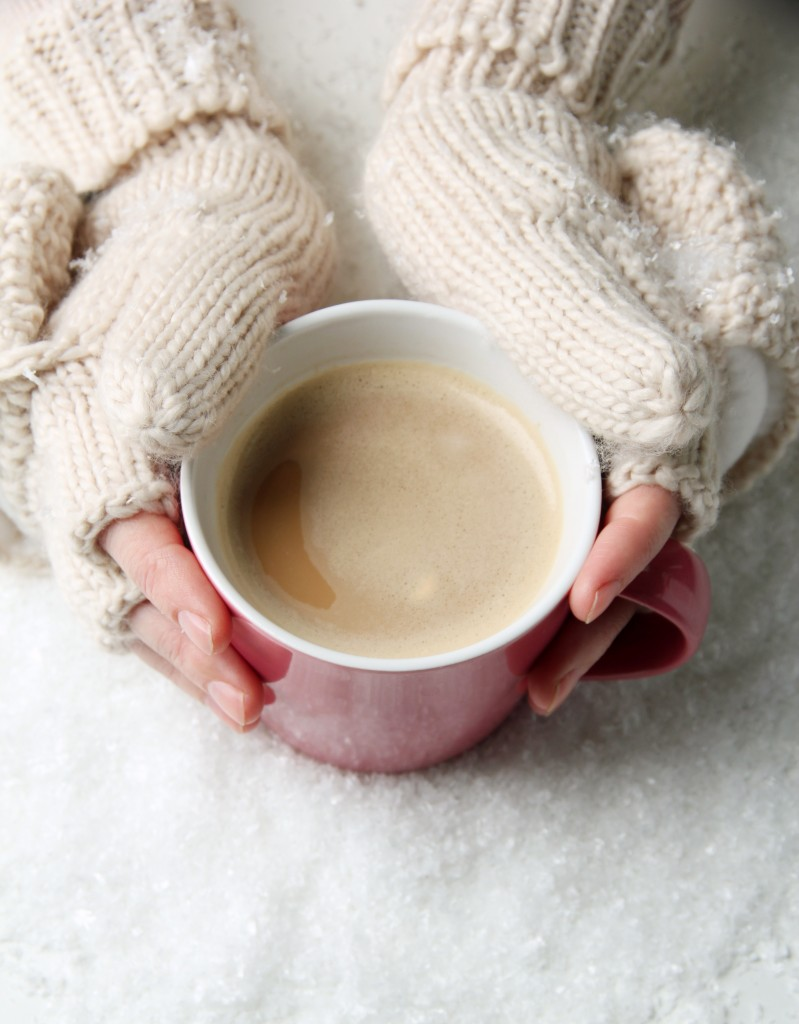 Two hands in winter gloves holding a mug of hot cocoa