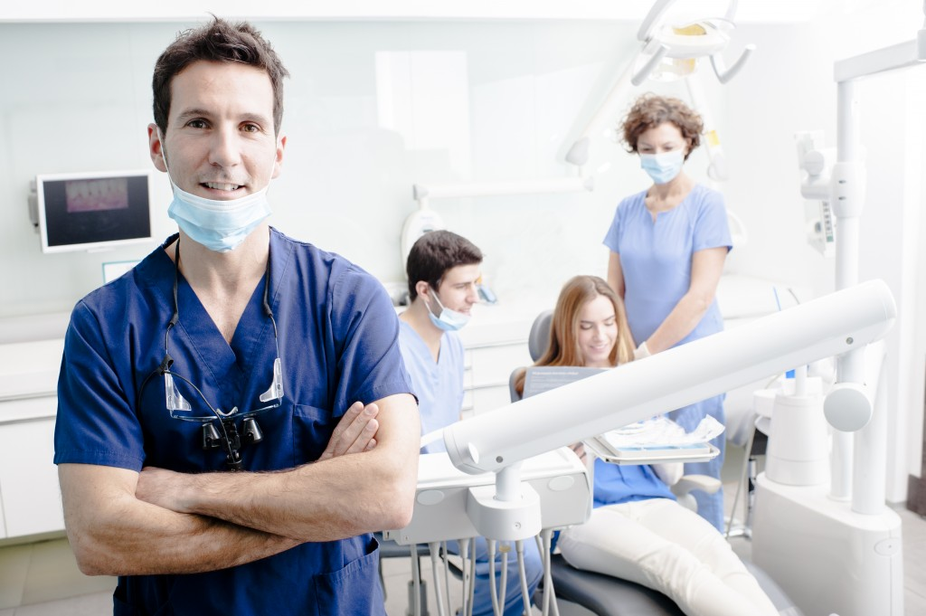 Dentists and assistants speaking with dental patient during dental checkup