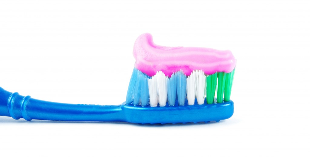 Line of pink toothpaste on the bristles of a blue toothbrush