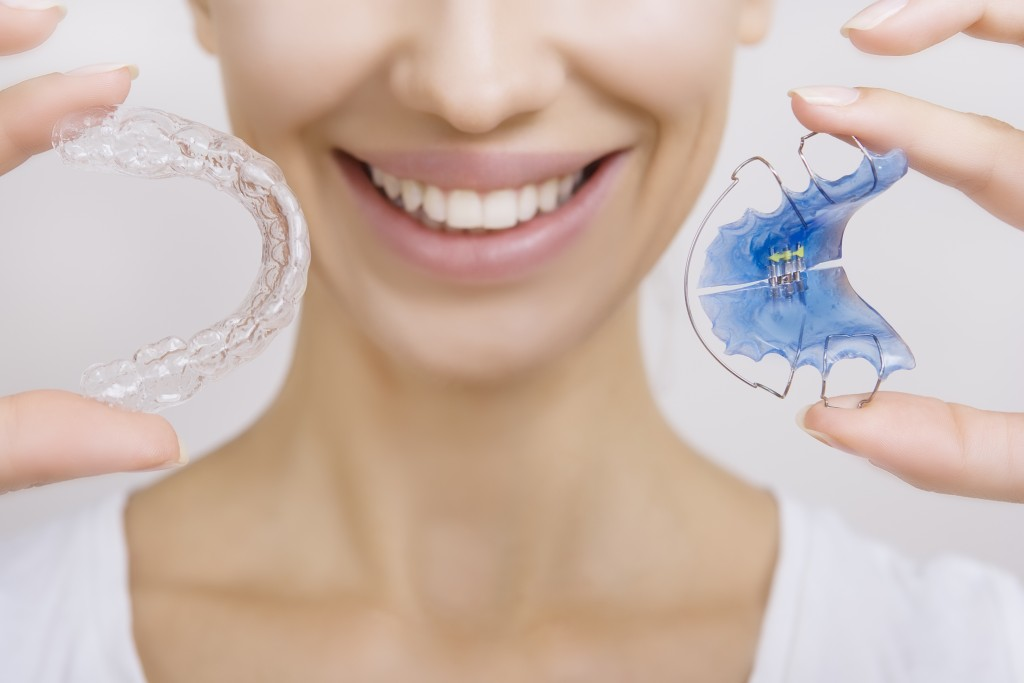 Smiling woman holding two different types of retainers
