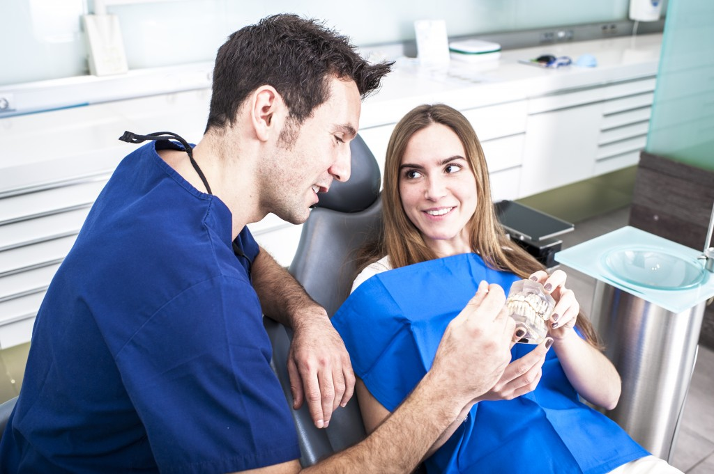 Male dentist speaking to female patient
