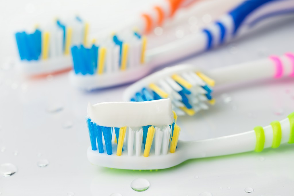 Four multi-colored toothbrushes with toothpaste.