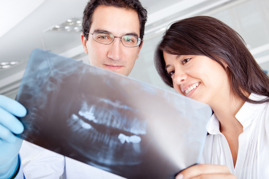 Male dentist and female patient viewing dental X-rays
