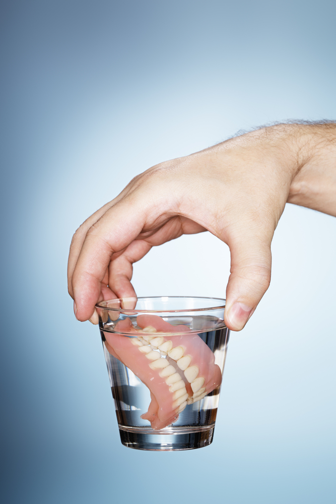man holding dentures in a glass of water