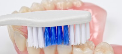 someone brushing dentures with a toothbrush
