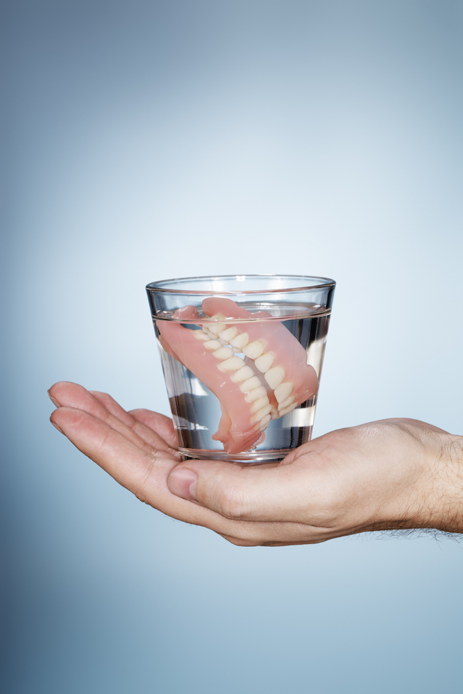 person holding a glass with dentures inside